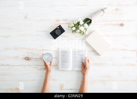 Women hands turn over book pages with glass of water, flowers and camera on the wooden desk - Stock Photo