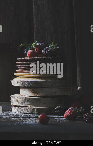 Rustic pancakes with organic fruits on wooden blocks with old wooden doors in backround - Stock Photo