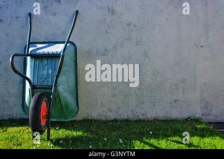 Wheelbarrow leaning against a wall. - Stock Photo