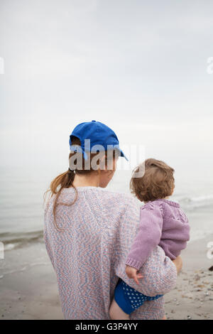Sweden, Skane, Osterlen, Mother carrying daughter (2-3) on beach - Stock Photo