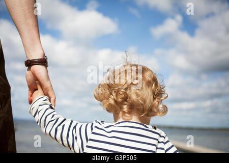 Sweden, Skane, Man holding his daughter´s (2-3) hand - Stock Photo