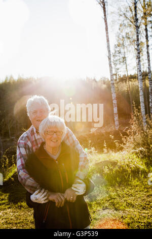 Sweden, Medelpad, Sundsvall, Senior couple standing in forest embracing - Stock Photo