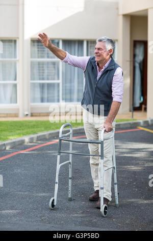 Senior man with walking frame waving his hand - Stock Photo