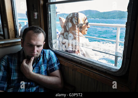 Passengers relaxing on a ferry that is travelling along the Bosphorus in Istanbul, Turkey - Stock Photo