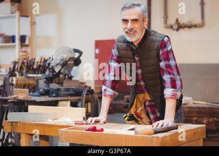 Portrait of senior carpenter leaning on a workbench - Stock Photo