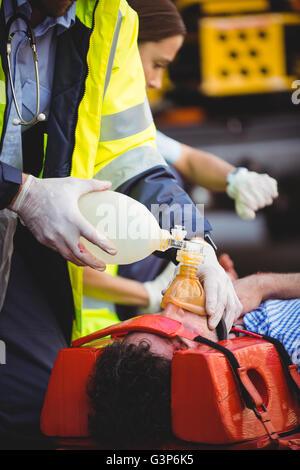 Ambulance man rescuing an injured man - Stock Photo