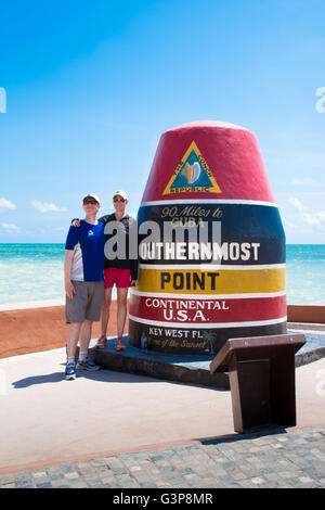 KEY WEST, FLORIDA - APRIL 26, 2016: Visitors pose for photograph at the Southernmost Point Monument in Key West - Stock Photo
