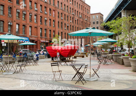 Urban square in Brooklyn under the Manhattan Bridge with patio chairs and art installation called Heart Seat - Stock Photo