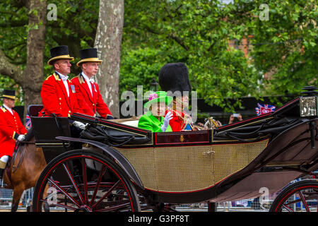 The Queen in a bright green outfit rides with The Duke Of Edinburgh in a carriage along The Mall at The Trooping - Stock Photo