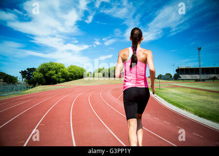 Composite image of rear view of woman running against white background - Stock Photo