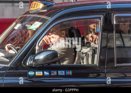 A black cab driver sitting in sunlight in busy traffic in London with a male passenger behind him. The taxi has - Stock Photo