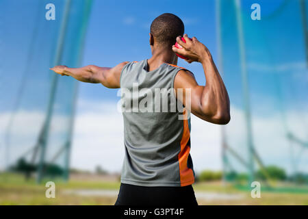 Composite image of rear view of athletic man preparing the shot put - Stock Photo