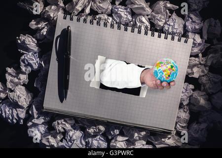 Composite image of businessman holding globe - Stock Photo