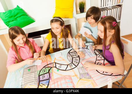 Top view of four kids playing the tabletop game - Stock Photo