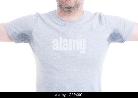 Man with both arms raised and excessive sweat stains on grey t-shirt isolated on white as hyperhidrosis concept - Stock Photo