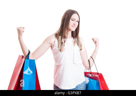 Cheerful smiling woman holding shopping bags act like a winner isolated on white background - Stock Photo