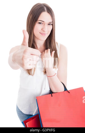 Great sales concept with smiling shopping female showing thumb up and holding colored gift bags isolated on white - Stock Photo