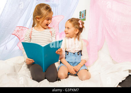 Two little pixies with wings reading bedtime story - Stock Photo