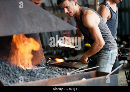 Young farriers at work in competition for making horse shoes at South of England Agricultural Show at Ardingly Showground - Stock Photo