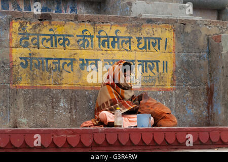 Unidentified Indian man sits on the steps of ghat near sacred river Ganges in Varanasi. - Stock Photo