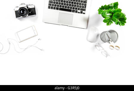 Workplace with laptop, phone, notebook, photo camera, green plant. Office desk white background. Hero header - Stock Photo