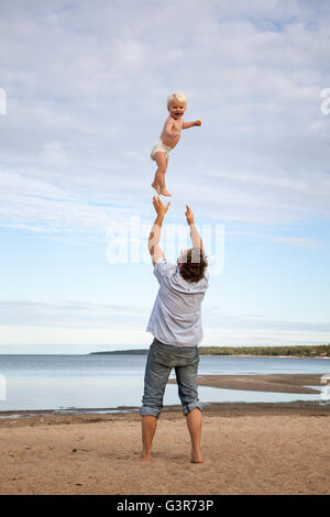 Sweden, Medelpad, Juniskarr, Man throwing son (2-3) in air - Stock Photo