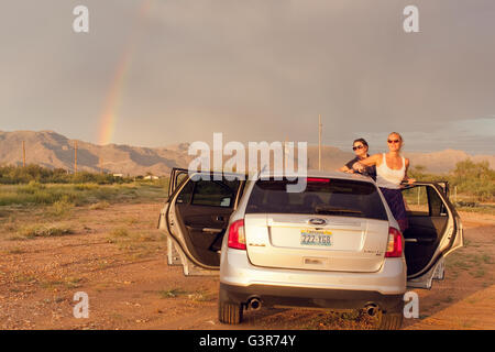 USA, California, Two female friends on road trip at sunset - Stock Photo