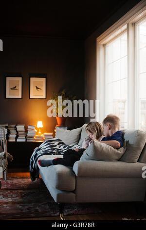 Denmark, Boy (8-9) and girl (4-5) sitting on sofa in living room