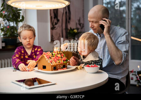 Sweden, Man and two boys (18-23 months, 4-5) decorating gingerbread house - Stock Photo