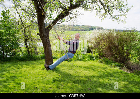 Sweden, Vastergotland, Senior man sitting on rope swing - Stock Photo