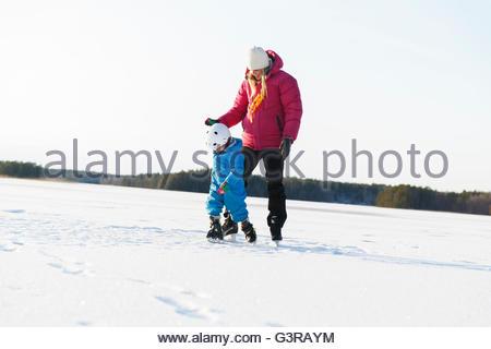 Sweden, Sodermanland, Jarna, Mother teaching son (2-3) ice skating on frozen lake - Stock Photo
