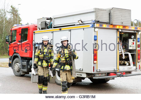 Sweden, Sodermanland, Fire-fighters by fire engine - Stock Photo