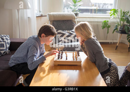 Sweden, Boy (12-13) and girl (10-11) playing chess in living room - Stock Photo