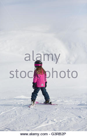 Sweden, Vasterbotten, Hemavan, Little girl (6-7) in ski wear standing on mountain slope - Stock Photo