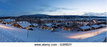 Sweden, Vasterbotten, Hemavan, Wooden houses at ski resort at dusk - Stock Photo