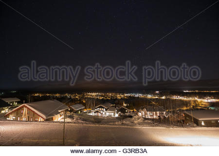Sweden, Vasterbotten, Hemavan, Wooden houses at ski resort at night - Stock Photo
