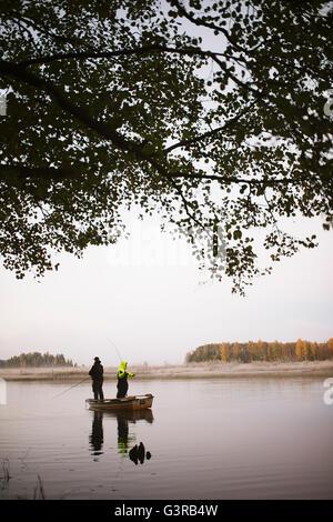 Sweden, Vastmanland, Bergslagen, Torrvarpen, Young men fishing in lake at sunset - Stock Photo