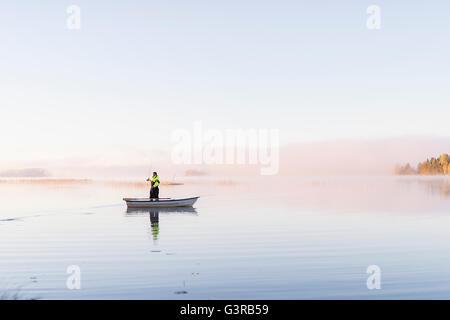 Sweden, Vastmanland, Bergslagen, Torrvarpen, Young man fishing in lake at sunset