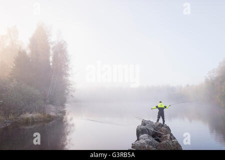 Sweden, Vastmanland, Bergslagen, Torrvarpen, Young man fishing in lake on foggy day