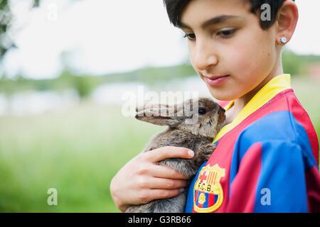 Sweden, Varmland, Filipstad, Gasborn, Horrsjon, Boy (10-11) in sport jersey holding rabbit - Stock Photo