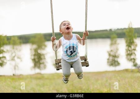 Sweden, Varmland, Filipstad, Gasborn, Horrsjon, Boy (2-3) playing on swing - Stock Photo
