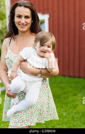 Sweden, Varmland, Filipstad, Gasborn, Horrsjon, Portrait of mother holding baby girl (12-17 months) - Stock Photo