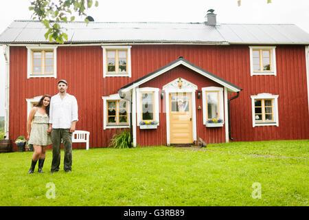 Sweden, Varmland, Filipstad, Gasborn, Horrsjon, Couple standing in front of house - Stock Photo