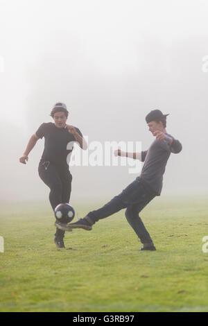 Sweden, Vastmanland, Teenage boys (14-15) playing soccer - Stock Photo