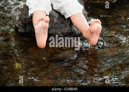 Sweden, Vastmanland, Baby boy (18-23 months) dipping feet in water - Stock Photo