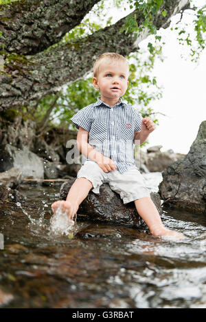 Sweden, Vastmanland, Baby boy (18-23 months) dipping feet in water - Stock Photo