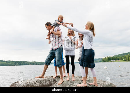 Sweden, Vastmanland, Bergslagen, Hallefors, Nygard, Family with four children standing on rock - Stock Photo