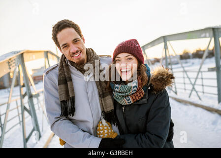 Sweden, Vasterbotten, Umea, Young couple on footbridge in winter - Stock Photo