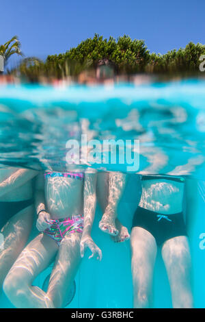 Italy, Sardinia, Alghero, Mother with children (14-15, 16-17) at swimming pool - Stock Photo