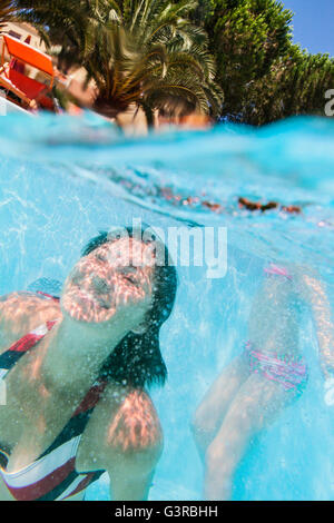 Italy, Sardinia, Alghero, Mother and daughter (14-15) diving in swimming pool - Stock Photo